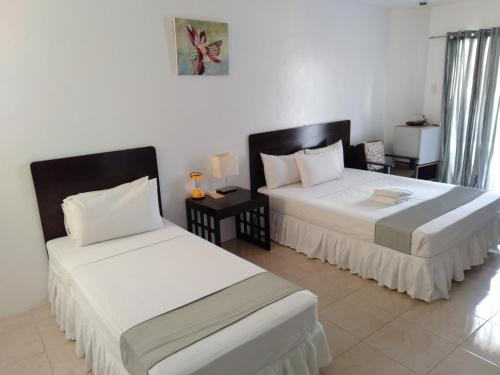 A bed or beds in a room at Boracay White Coral Hotel
