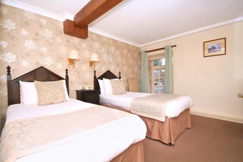 A bed or beds in a room at The Watermill Hotel