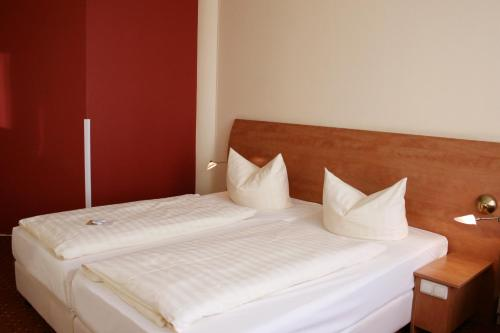 A bed or beds in a room at Hotel Mercator Itzehoe-Klosterforst