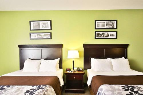 A bed or beds in a room at Sleep Inn & Suites University