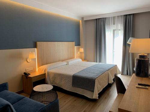 A bed or beds in a room at Hotel Puerta del Mar