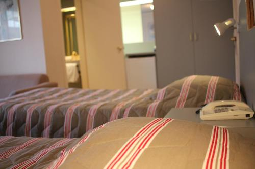 A bed or beds in a room at Beaumaris Bay Motel