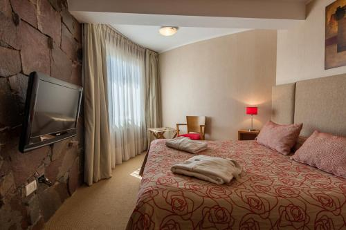 A bed or beds in a room at Marcin Hotel