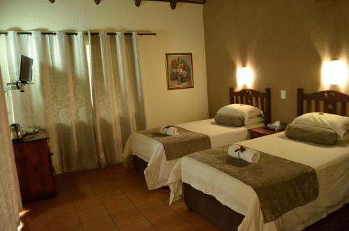 A bed or beds in a room at Acasia Guest Lodge