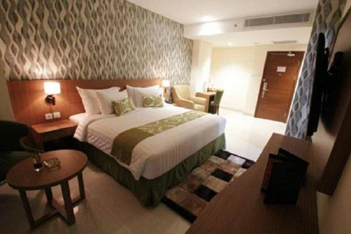 A bed or beds in a room at Ijen Suites Resort & Convention