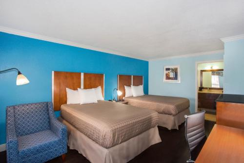 A bed or beds in a room at Days Inn by Wyndham Florida City