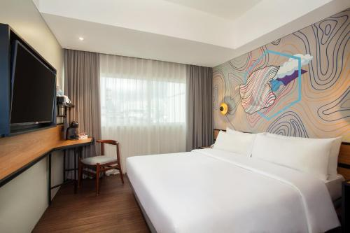 A bed or beds in a room at Swiss-Belinn Wahid Hasyim