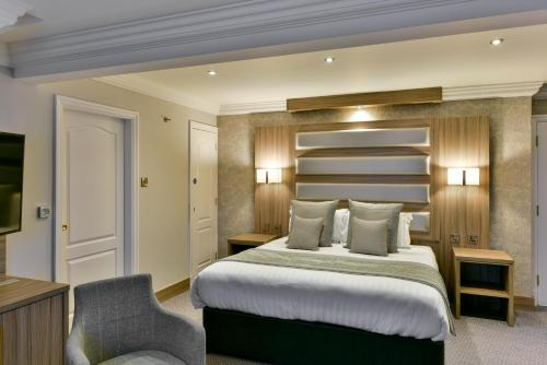 A bed or beds in a room at Best Western Manchester Oldham Smokies Park Hotel