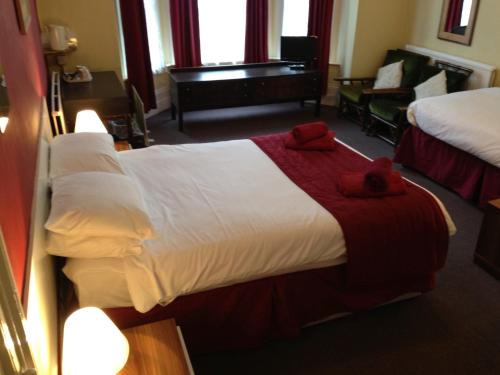 A bed or beds in a room at Abbey Lodge Hotel - B&B
