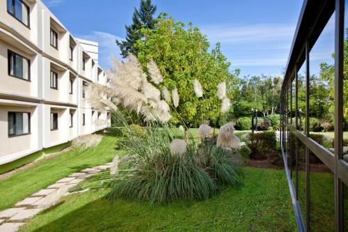 A garden outside ibis Styles Chalon sur Saône