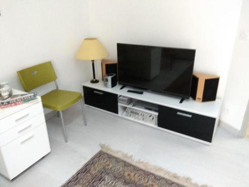A television and/or entertainment centre at Les Toits du Prado