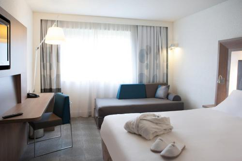 A bed or beds in a room at Novotel Fontainebleau Ury