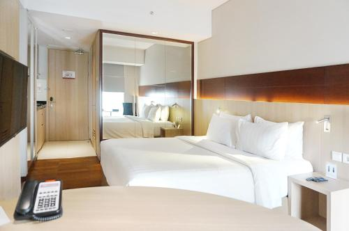 A bed or beds in a room at Ra Premiere Simatupang Jakarta
