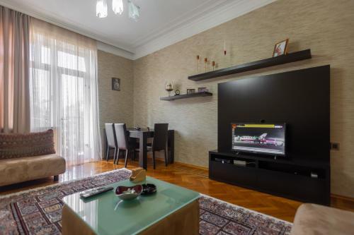 Uma TV ou centro de entretenimento em Azneft Square Flame Towers View Apartment