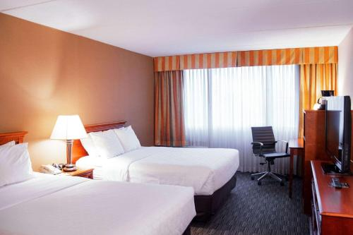 A bed or beds in a room at Clarion Hotel and Conference Center - Joliet