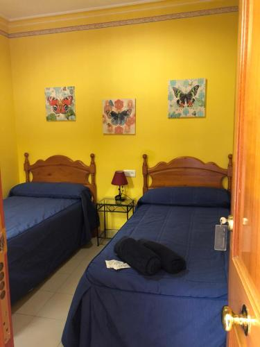 A bed or beds in a room at Pensión Macarena