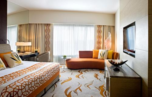A bed or beds in a room at Millennium Al Rawdah Hotel