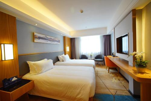 A bed or beds in a room at Guangzhou Lilium Elysees Hotel