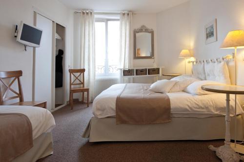 A bed or beds in a room at Le Kléber Hôtel