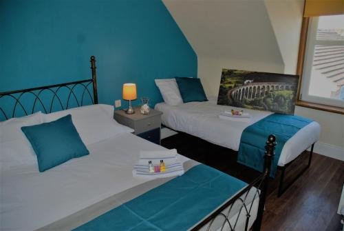 A bed or beds in a room at The Coo's Guest House