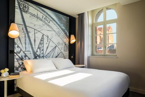 A bed or beds in a room at Mercure Beauvais Centre Cathédrale