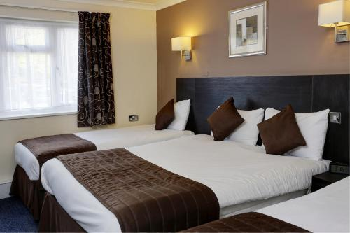 A bed or beds in a room at BEST WESTERN Gatwick Skylane Hotel