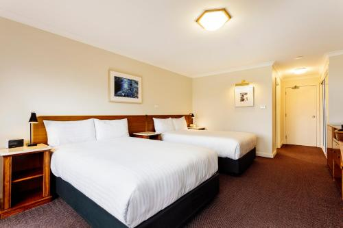 A bed or beds in a room at Cradle Mountain Hotel