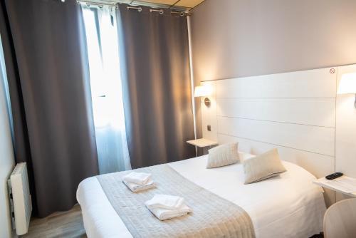 A bed or beds in a room at Hôtel Garabel