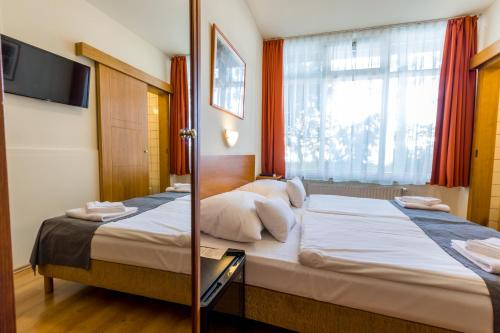 A bed or beds in a room at Budapest Csaszar Hotel