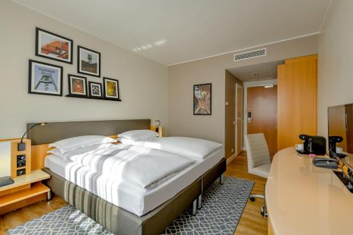 A bed or beds in a room at Mercure Hotel Bochum City