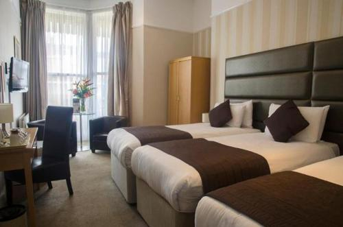 A bed or beds in a room at The Brighton Hotel