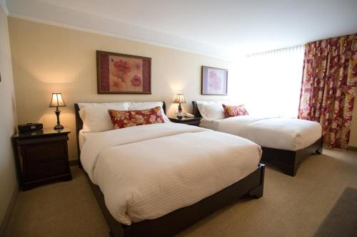 A bed or beds in a room at Le St-Martin Bromont Hotel & Suites