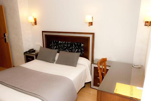 A bed or beds in a room at Abadía Burgos Camino Santiago