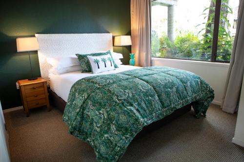 A bed or beds in a room at Emerald Inn on Takapuna Beach