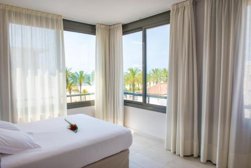 A bed or beds in a room at Atenea Park Suites & Apartments