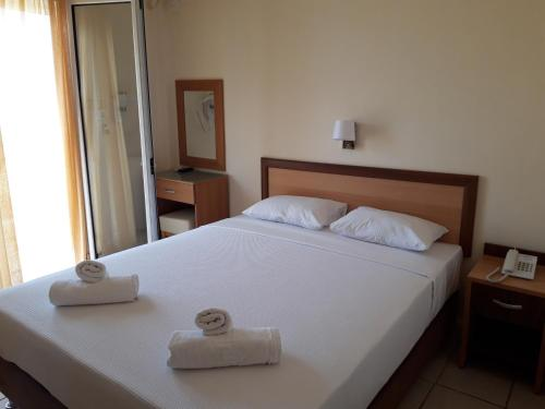 A bed or beds in a room at Vourvourou Hotel