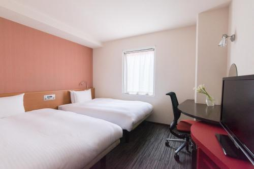 A bed or beds in a room at the b kobe