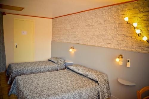 Un ou plusieurs lits dans un hébergement de l'établissement Hotel Les Pins