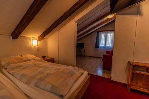 A bed or beds in a room at Hotel Weisshorn