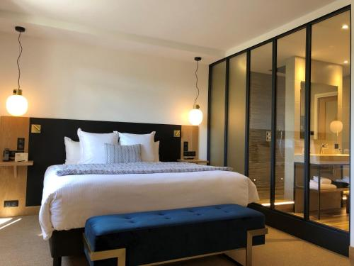 A bed or beds in a room at Hostellerie Cèdre & Spa Beaune