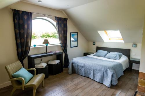 A bed or beds in a room at La Ferme de l'Oudon & SPA