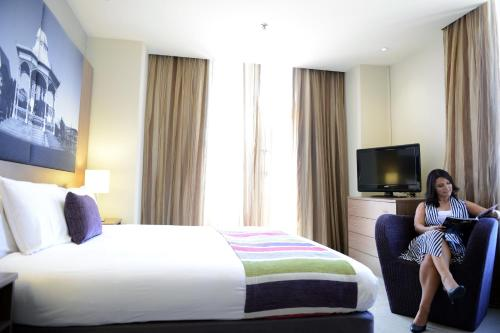 A bed or beds in a room at Grosvenor Hotel Adelaide