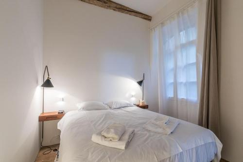 A bed or beds in a room at L'Arsenal - très bel appartement sur le Vieux-Port