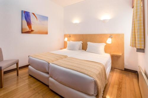 A bed or beds in a room at Apartamentos Turisticos Pinhal Da Marina