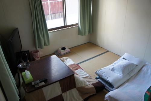 A bed or beds in a room at Miyoshiya Ryokan