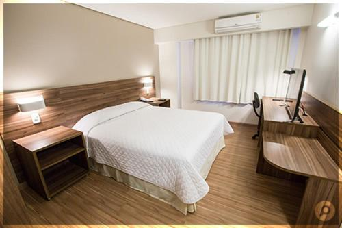 A bed or beds in a room at Mogano Business