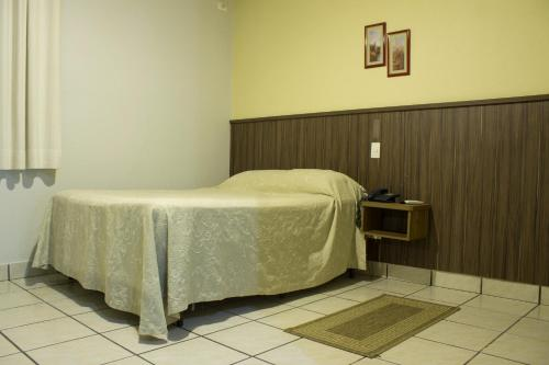 A bed or beds in a room at Rio Claro Plaza Hotel