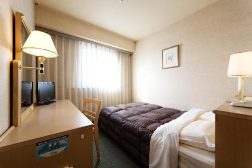 A bed or beds in a room at Kurume Washington Hotel Plaza