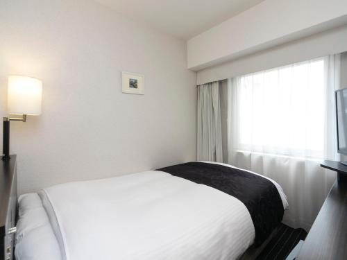 A bed or beds in a room at APA Villa Hotel Yodoyabashi