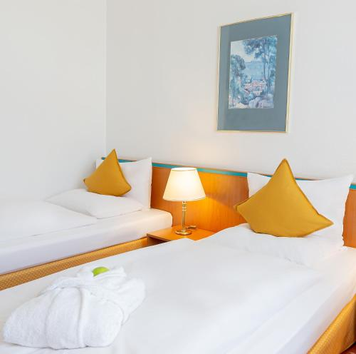 A bed or beds in a room at Dorint Hotel Leipzig